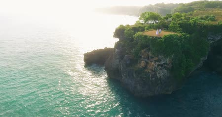 footage happy couple at cliff Bali by drone aerial view.
