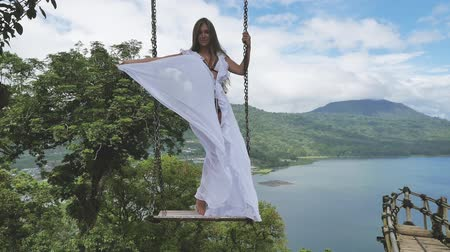 Sexy woman with health skin at swing wearing white swimsuit