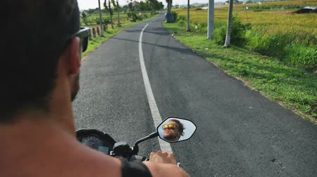 Man riding a motorcycle on the road, Indonesia, Bali.