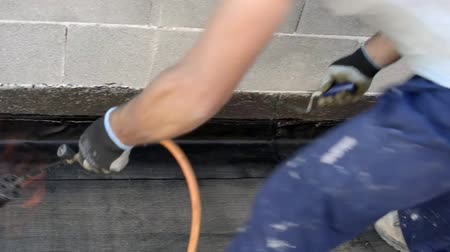 tető : Worker preparing part of bitumen roofing felt roll for melting by gas heater torch flame