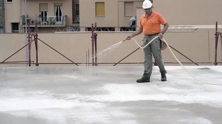 Construction worker watering fresh concrete slab using a hose Stock Footage