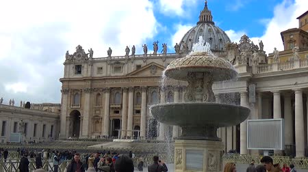 Vatican, Rome, ITALY - March 5, 2017: Tourists in the square St. Peter in Rome around a fountain. Some take pictures, others are doing selfies. In the background the dome playing the tolling of bells.