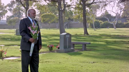 smutek : African American Middle Aged Male Standing With Flowers in Cemetery. Camera dolly from right to left. Slow motion shot.