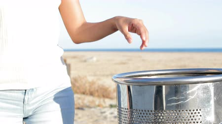 udržitelnost : Close up of a woman hand throwing trash into a bin walking on the beach