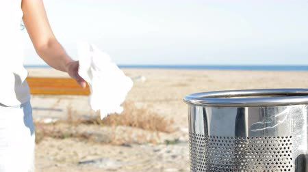 errado : Close up of a woman hand throwing trash on the floor on the beach Stock Footage