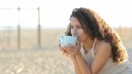 diverso : Happy latin woman drinking coffee on the beach at sunset enjoying flavor in slow motion