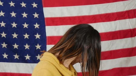 zászló : young brunette with blue glasses in front of an american flag, slow motion Stock mozgókép