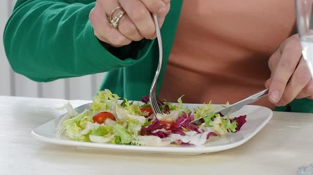 young woman eating a salad, close up of hands