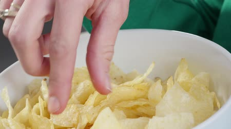 játékpénz : woman eating chips, close up Stock mozgókép