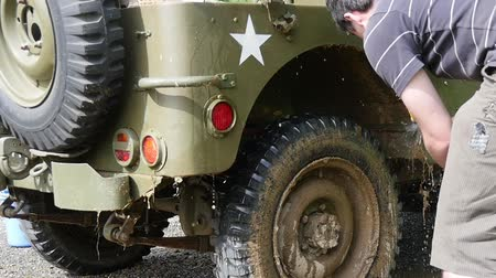 por que : young man cleaning the military vehicle, slow motion Stock Footage
