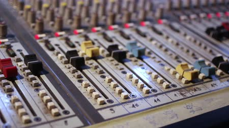 amplificador : Dolly shot of an old sound board, mixing console with nobs and sliders.