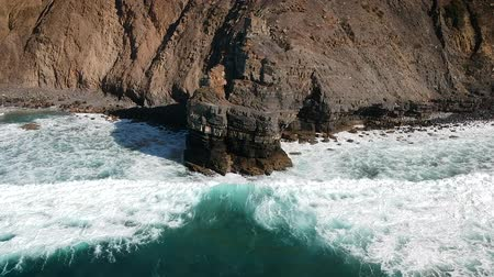 lagos : Aerial done shot of whitewater waves hitting a cliff on the shore of a beach in Algarve, Portugal.