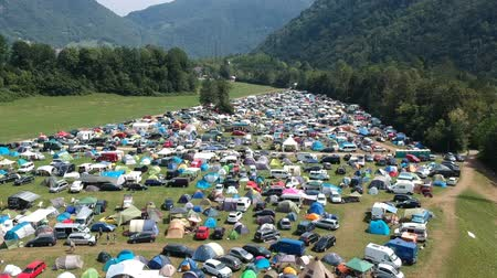 eco tourism : Aerial drone shot of a camping ground at a music festival in a green and lush mountainous area.