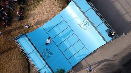deskorolka : Aerial drone shot of a male skateboarder doing tricks at a contest in a miniramp. Wideo