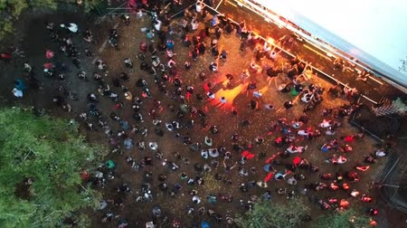 korhadt : Aerial drone shot of a crowd watching an outdoor concert event at a festival with flashing lights in a forest.