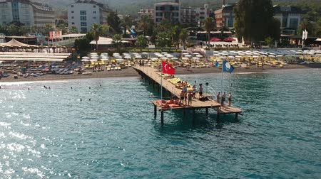 denizciler : Aerial drone shot of people swimming and sunbathing on a pier at a hotel beach in Kemer, Turkey. Stok Video