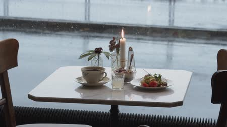 неформальный : A breakfast on a lonely table at a cafe on a rainy day.