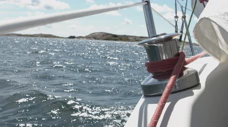 lanoví : A winch on the railing of the deck of a white sailing boat at sea - slowmotion footage.