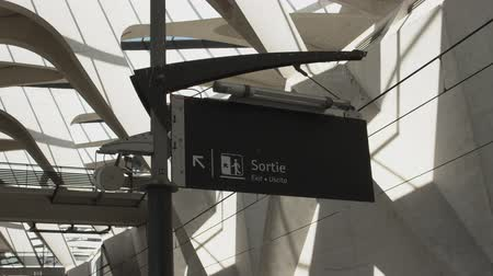 indicating : An exit sign on a platform at a train station in France.