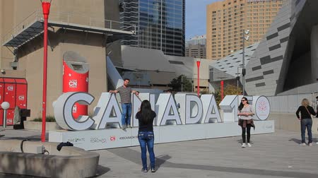 jubileu : Toronto, Canada - Oct 21, 2017: Tourists taking pictures at the Canada 150 celebration sign in front of the CN Tower in Toronto.