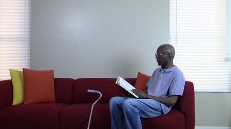 czarne : Senior citizen relaxing on the couch while reading a book Wideo