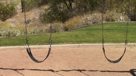 Pair of empty swings in a playground in Mesa, Arizona
