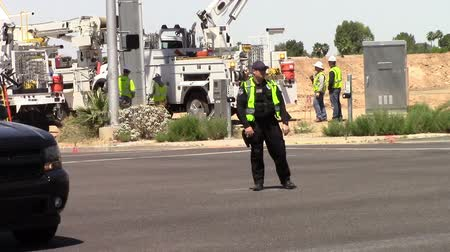 Mesa, Arizona, USA - April 20, 2015:  A Mesa Policeman directing traffic due to construction in background. Traffic lights are out. Taken April 20, 2015