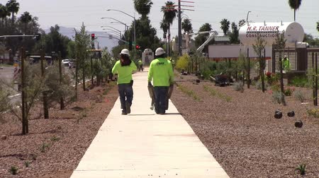 Mesa, Arizona, USA - April 20, 2015:  Two construction workers walking down the street pushing a wheelb arrow on the job site of new homes. Taken April 20, 2015 Dostupné videozáznamy