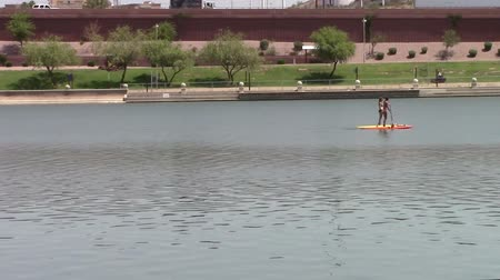 Tempe Town Lake, Arizona. Two females paddle boarders floating down the lake.