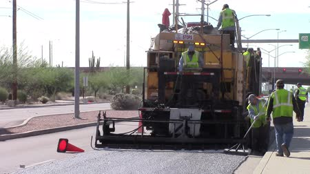 Mesa, Arizona, USA - October 30, 2015: Highway workers paving roadway with new sealant.
