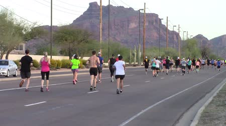 arka görünüm : Mesa, Arizona, USA - February 27, 2016: Runners from all over the US participated in the BMO Harris Bank Marathon.Rear view of runners participating in a marathon Stok Video