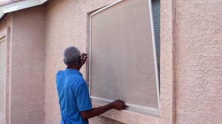 A senior man installing a window screen on house