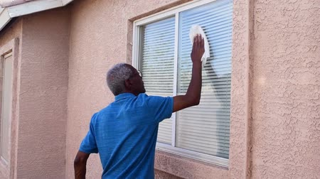 мастер на все руки : A senior man is washing home windows for the summer or spring seasons