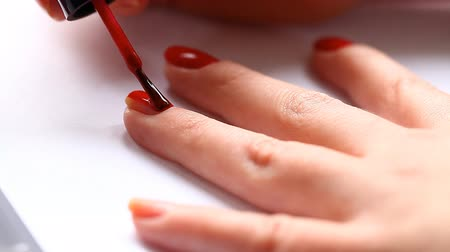 nehet : woman paints her nails with red lacquer