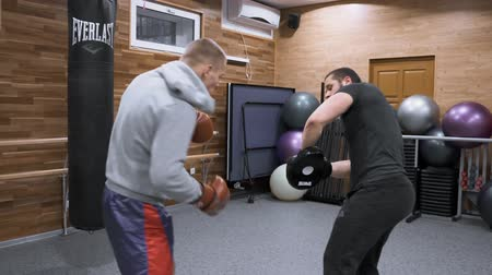puncs : Two young male boxers are training in the gym. Kyiv UA, 28-03-2019