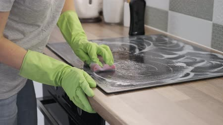 induction cooker : Closeup of hand woman cleaning modern cooking glass ceramic electric surface with sponge and detergent