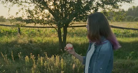 Young beautiful girl walking and eating red apple, nature sunset landscape
