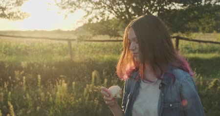 Young happy girl walking and eating red apple, natural healthy food on nature, rural landscape golden hour Stok Video