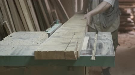 Closeup of wood plank on woodworking machine in a carpentry workshop, carpenter using plane.