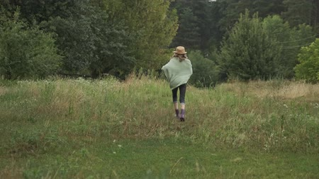 Running girl child in hat knitted blanket boots, back view. Nature background trees, summer grass, country style Stok Video