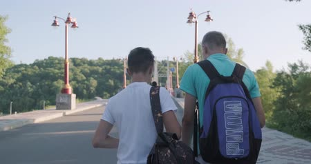 socialising : Kyiv UA, 31-07-2019. Two friends teenage boys walking and talking on foot bridge, view from the back, sunny summer day sunset