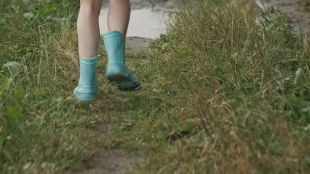 mischief : Close-up of running legs in boots, run along country road and stepping on small rain puddle, dirty splashes