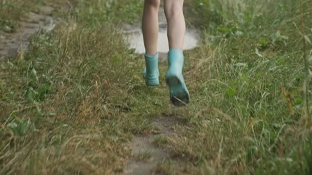Close-up of legs in boots of girl running in summer rain puddle on country road Stok Video