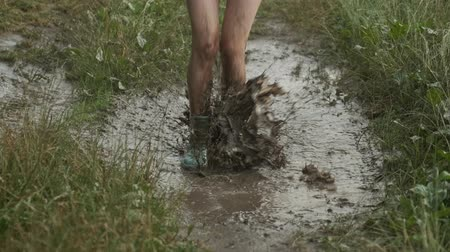 Close-up of girl legs in boots jumping in very muddy puddle, dirty spray