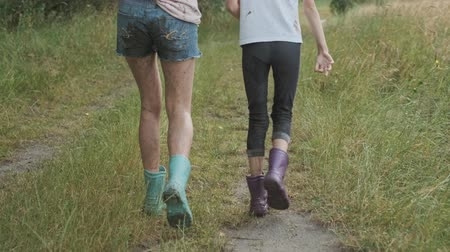 pocsolya : Two happy girls sisters walking after the rain in dirty clothes holding hands, children talking laughing, rural road summer nature background back view