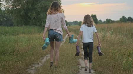 Two happy girls sisters walking after the rain in dirty clothes with rain boots in hands, children talking laughing, rural road summer nature background back view Stok Video