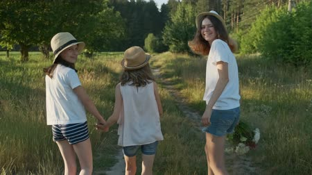 verhuizen : Children three girls in hats holding hands walking back along the rural country road, beautiful summer landscapes of nature, golden hour Stockvideo