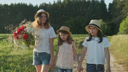 Children are three girls with bouquet of flowers holding hands walking along a country road, summer holidays in nature, beautiful landscape, golden hour