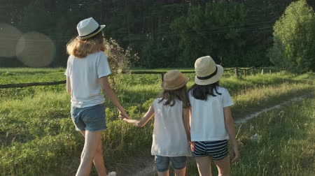 go away : Children three girls in hats holding hands running back along the rural country road, beautiful summer landscapes of nature, golden hour