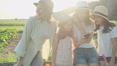 Happy mother with three daughters looking into the smartphone, family in nature, summer countryside landscape, golden hour